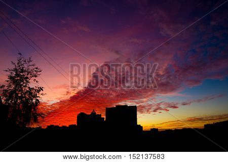 bright sunset and cirrocumulus with black city silhouette