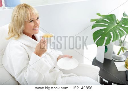 Wonderful morning. Happy mature woman is drinking healthy tea with pleasure at wellness center. She is sitting in bathrobe and smiling