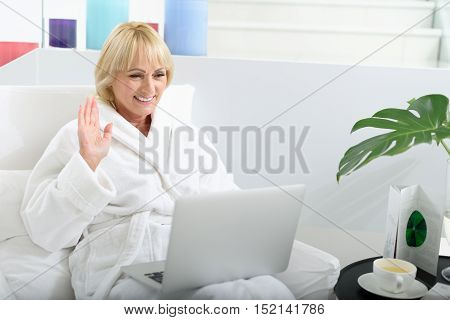Hello. Happy mature lady is communicating in online by laptop on vacation. She is waving hand and smiling. Lady is wearing white bathrobe