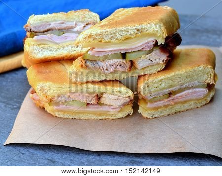Cuban Sandwiches stacked on a piece of brown paper. Close up showing ingredients use for the Cubanos; pork, ham, Swiss cheese, pickles and mustard.
