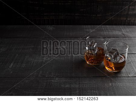 Glasses of whiskey with ice cubes on wooden background