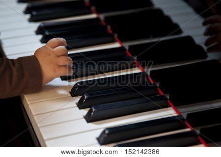 newborn kid hand trying to play classic piano