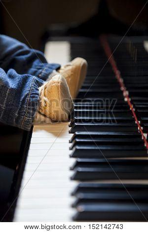 newborn kid feet trying to play classic piano