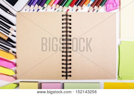 Top view of desktop with blank spiral notepad colorful suppliles and cellphone. Mock up