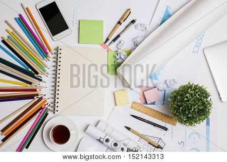 Top view of creative desktop with blank spiral notepad smartphone coffee cup decorative plant financial report and colorful supplies. Mock up