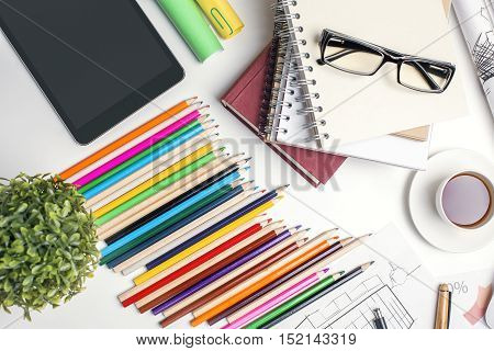 Top view of white office desktop with blank tablet colorful pencils coffee cup notepads glasses and other items. Mock up