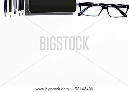 Top view of white desktop with tablet glasses and supplies. Mock up