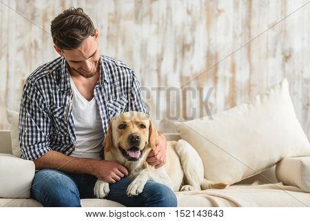 smiling handsome guy sitting on a couch with a puppy indoors