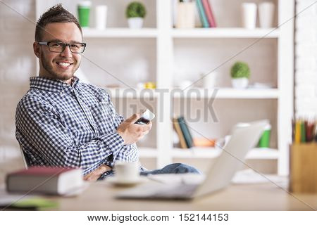 Portrait of attractive young caucasian man using cell phone while sitting at office table with laptop computer and other items