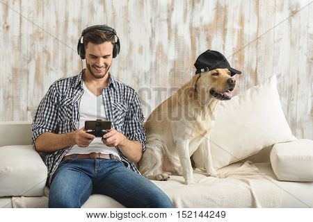 handsome boy playing with gamepad on smartphone in headphones while dog sitting in a baseball cap