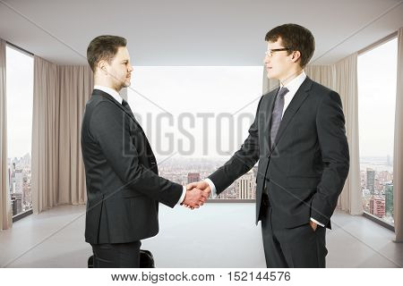 Two handsome businessmen in suits shaking hands in modern interior with city view. Partnership concept
