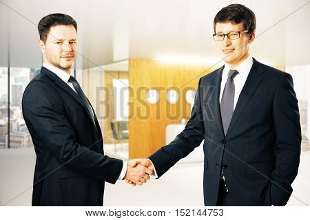 Handsome happy businessmen shaking hands in modern office. Partnership concept