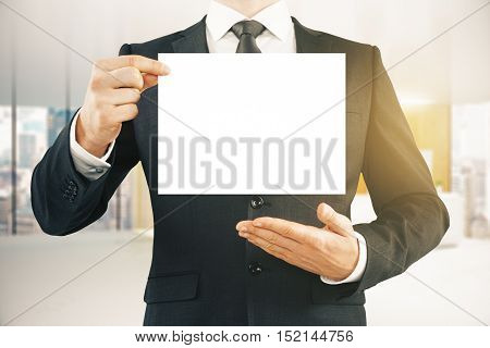 Close up of businessman in suit holding empty paper sheet in modern office interior. Mock up. Presentation concept