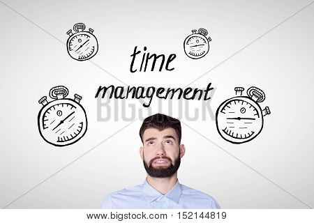 Portrait of worried young man on light background with creative clock skethes. Time management and deadline concept