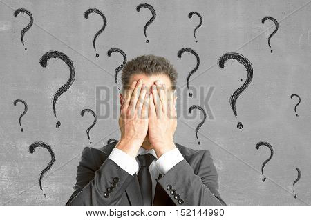 Young businessperson covering face with palms on concrete background with question mark sketches. Failure and fear concept