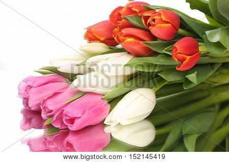 The fresh bouquet of tulips lies on a glossy surface with reflection