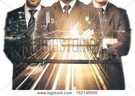 Silhouettes of three businessmen in suits and with folded arms on abstract night city road background. Double exposure. Teamwork partnership and leadership concept