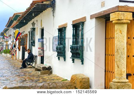 VILLA DE LEYVA COLOMBIA - APRIL 27: Old man sitting on a bench in the colonial town of Villa de Leyva Colombia on April 27 2016