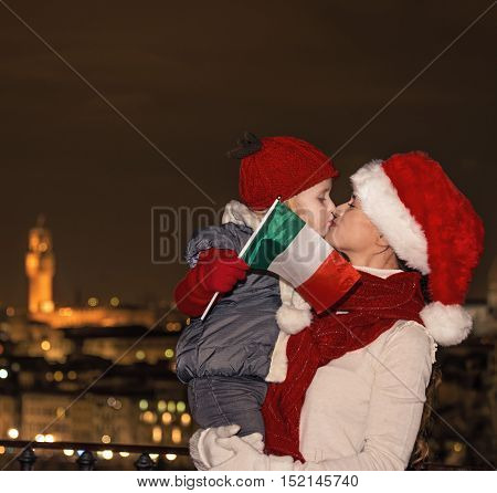 Mother And Child In Christmas Hats With Italian Flag Kissing
