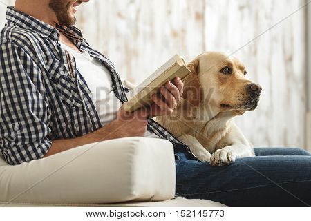 man holding a book and reading it while his labrador resting next to him