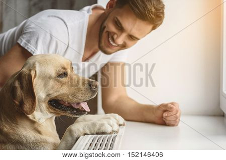 side view of a labrador retriever looking thru window and its owner smiling