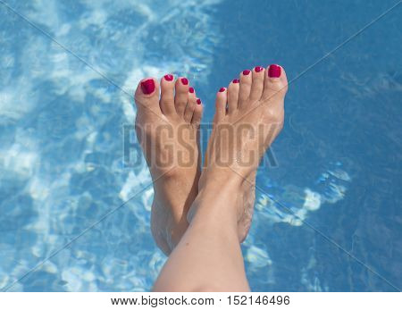 Feet and legs of woman in a summer pool