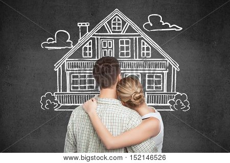 Back view of young couple looking at house sketch on dark concrete background. Mortgage and property concept