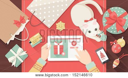 Woman purchasing Christmas gifts online using a tablet her cat is playing with a bauble on the desk holiday and celebrations banner