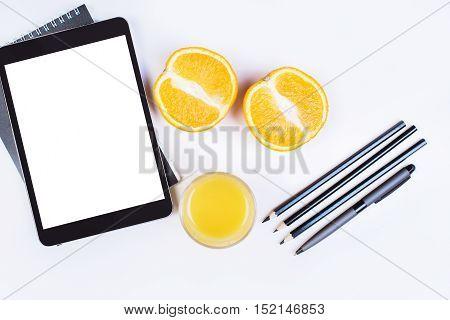 Top view of white desktop with digital tablet orange juice and fruit halves pencils and pen. Mock up
