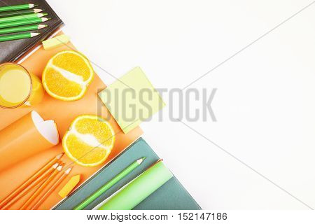 Top view of white desktop with orange halves stationery items and copy space