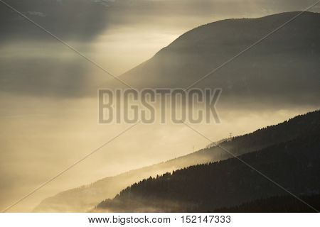Mountains with mysterious light filtering through the clouds