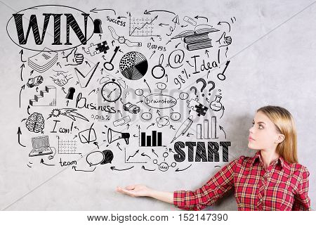 Side view of pretty young woman showing creative business sketch drawn on concrete wall. Success concept