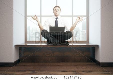 Meditating businessman with laptop in interior. 3D Rendering