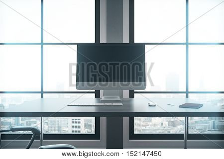 Closeup of modern workplace with blank computer screen keyboard notepad and other items in interior with large windows and city view. Mock up 3D Rendering