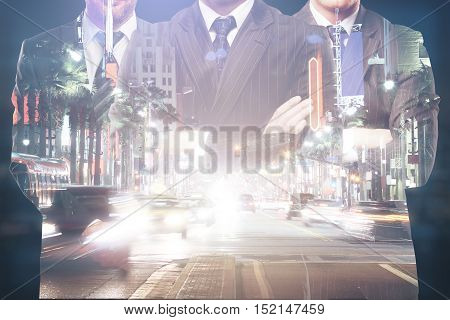 Silhouettes of three businessmen in suits and with folded arms on abstract night city background. Double exposure. Teamwork partnership and leadership concept