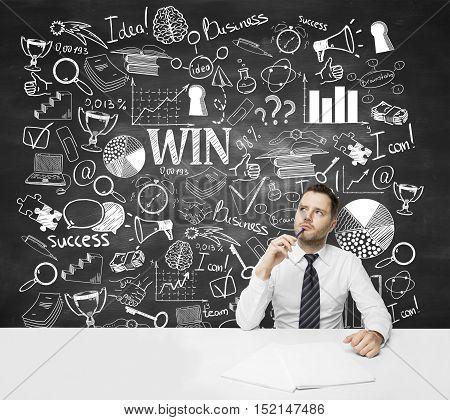 Thoughtful and confused young businessman at workplace with creative business sketch on chalkboard background. Success concept