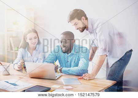 Team work. Three young and happy students are working with laptop at desk in light room, photo with blur and film effect.