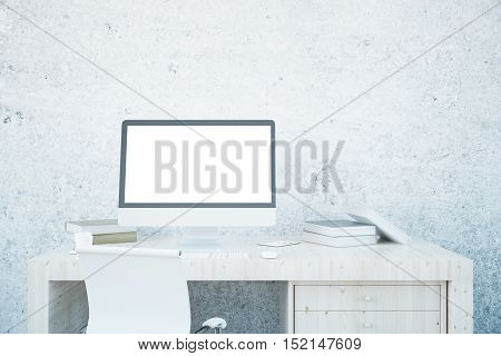 Front view of empty computer screen book and other items on light wooden desktop. Textured concrete wall background. Mock up 3D Rendering