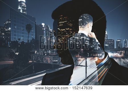 Thoughtful businessman on modern night city background. Double exposure