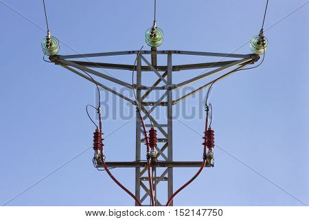 Front view of the top of a high voltage tower.