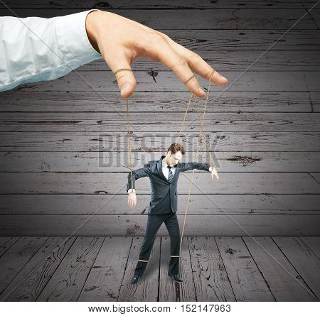 Hand controlling businessman as puppet on wooden background. Control concept