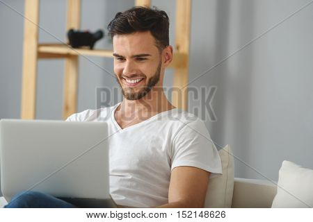 handsome brunet with laptop smiling and sitting indoors