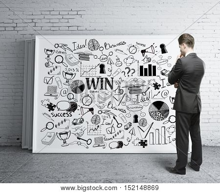 Back view of thoughtful young businessman in suit looking at business sketch drawn on whiteboard that is leaning on white brick wall. Research concept