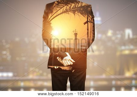 Back view of young businessperson dreaming about vacation on blurry night city background. Holidays concept. Double exposure