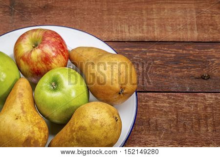 apples and pears on rustic red painted barn wood table with a copy space