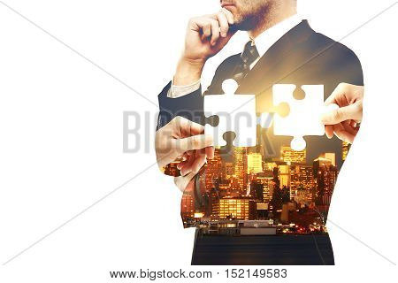 Thoughtful businessman on city background with puzzle pieces and copy space. Double exposure. Partnership and teamwork concept