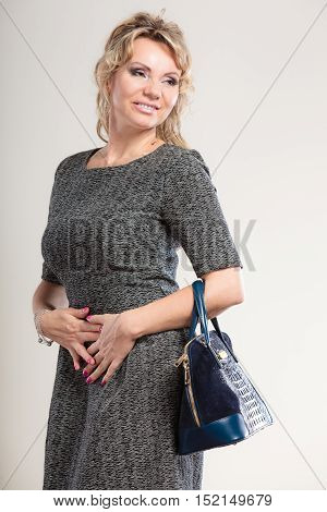 Women accessories fashion concept. Mature lady with handbag. Attractive woman wearing grey dress and has long blonde hair.