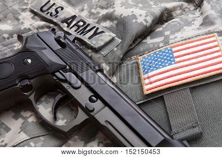 Close Up Studio Shot Of Handgun Over Usa Solder's Uniform And Shoulder Patch On It