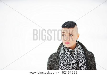 Portrait lovely cute girl with snowflakes on a short hair coat with a beautiful neck scarf on isolated background.