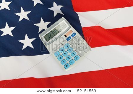 Studio Close Up Shot Of Ruffled National Flag With Calculator Over It - United States Of America